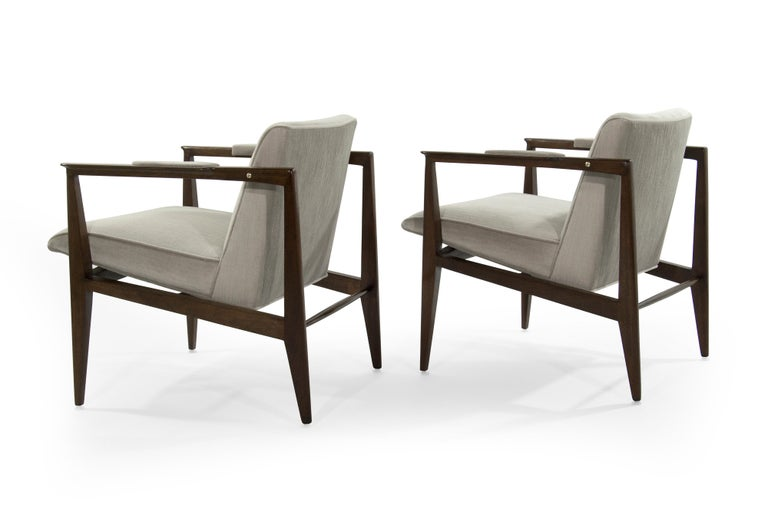Uncommon Dunbar armchairs composed of mahogany frames, brass accents and newly upholstered in natural mohair. Upholstered arm rests, original to the design, offer additional comfort. Brass has been polished, frames have been fully restored.