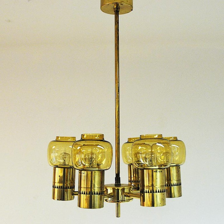 Brass and glass ceiling light with six lovely amber coloured glass domes designed by Hans-Agne Jakobsson for Markaryd Sweden circa 1950s. Base in brass with zig zag patterns. Measures: ca 60 cm H x 28 cm D. Good vintage condition.  Hans- Agne