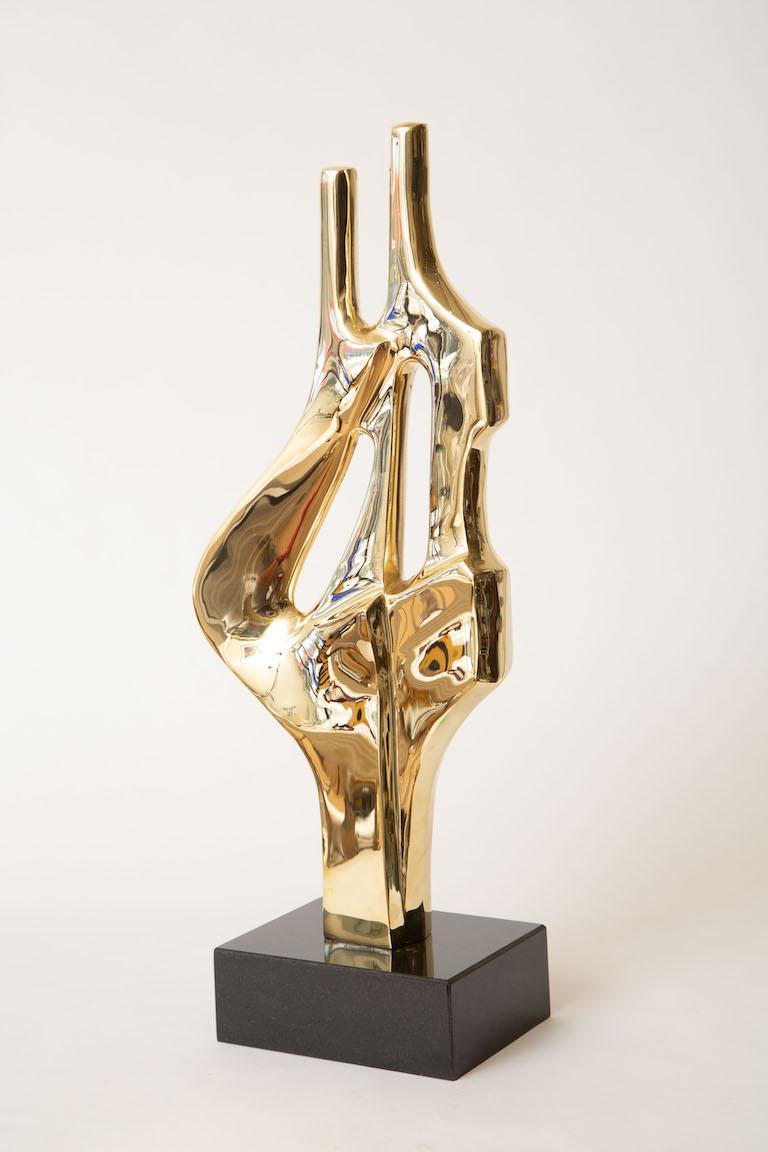 This tall fabulous polished brass abstract sculpture has been put on a new black granite base. It is vintage from the 70's and has 2 interconnected abstract bodies. The brass has been polished professionally. Sorry the photos do not do justice.