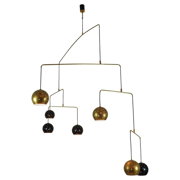 Original Italian brass mobile chandelier manufactured in a very small handcraft production in Milano,  Large, magic and poetical mobile chandelier with brass and black suspending spheres, it can moves with the flow of air. Wholly in balance