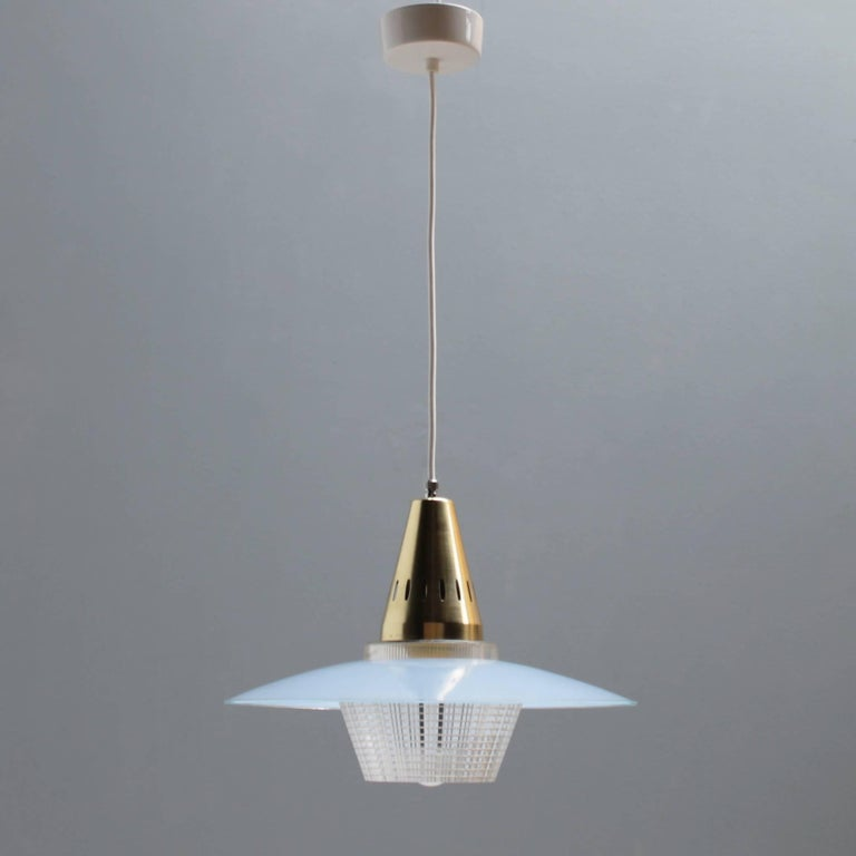 Charming pendant in manner of Stilnovo. Austria or Italian but the design is unknown to me. Blue glass shade with a brass gilt aluminium fixture with a plastic light diffuser. White porcelain canopy.