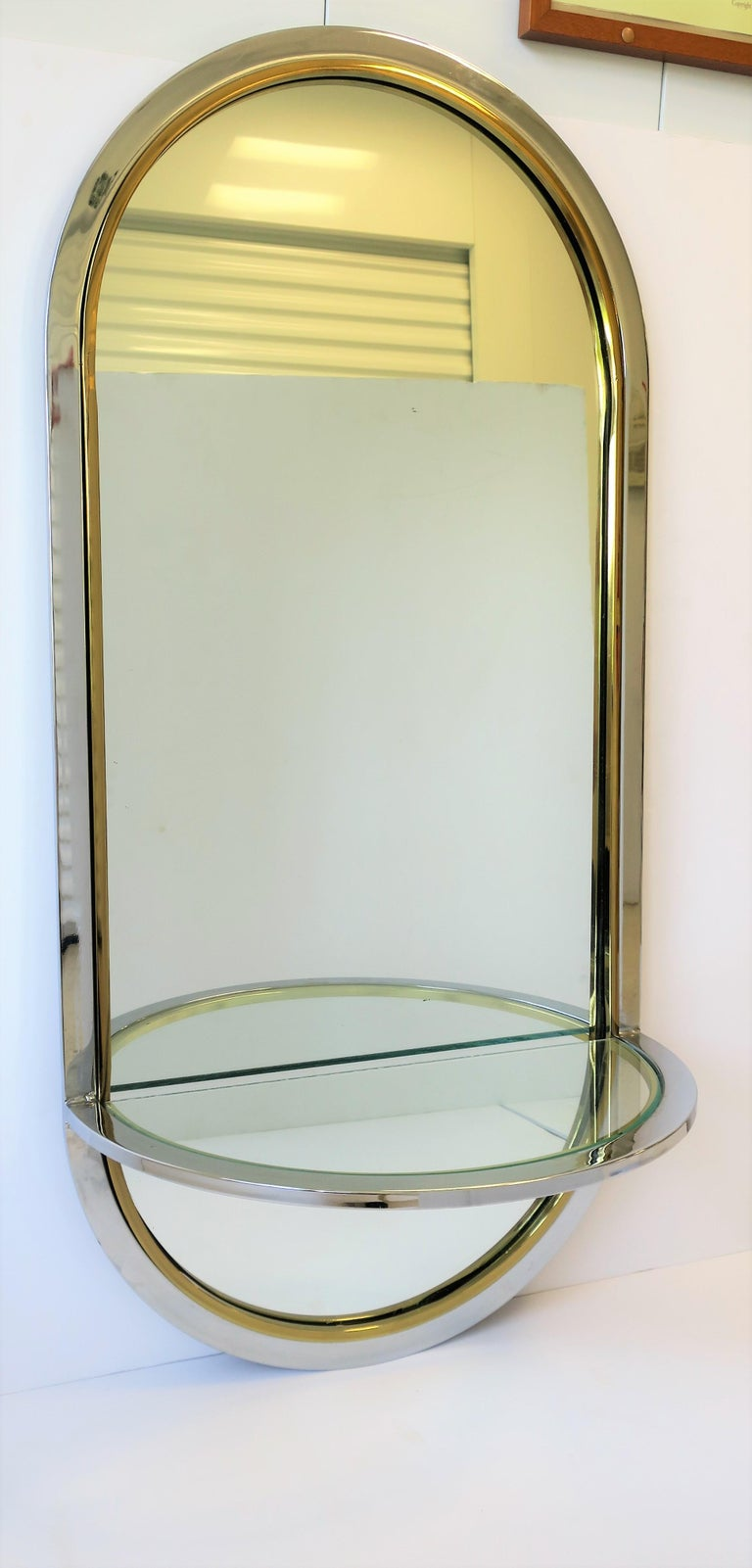 A beautiful Postmodern or '70s Modern style brass and chrome vanity, foyer or hall wall mirror with circular top and bottom, and demilune console shelf, circa late 20th century. Wall mirror's demilune glass shelf is held by its chrome and brass