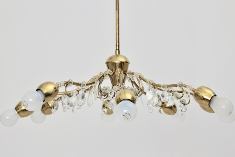 This lovely chandelier, which was designed and manufactured by the firm J & L Lobmeyr Vienna in the 1950s shows a brass chandelier frame.