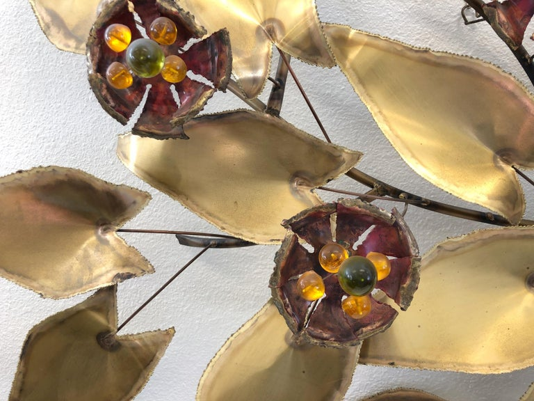 """A spectacular 1970s large brass and enamel wall sculpture in the manner of Curtis Jeré. The sculpture is constructed of torch cut solid brass. The flowers are enamel and yellow and green acrylic balls.   Dimensions: 54"""" wide 42"""" high 10.5"""" deep."""