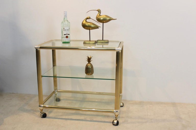 Stunning Belgian bar cart in brass and glass with tempered transparent glass. The heavy metal frame has a total original brass finish with silver plated edges with some patina. The table features three tiers, the middle one is flexible. The cart is