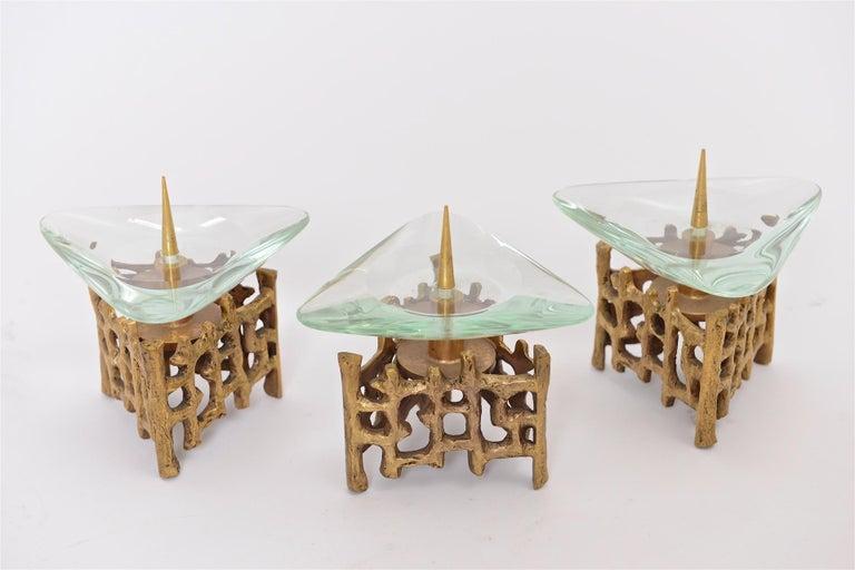 Three brass and glass candlesticks.  Attributed to Fontana Arte, circa 1960.