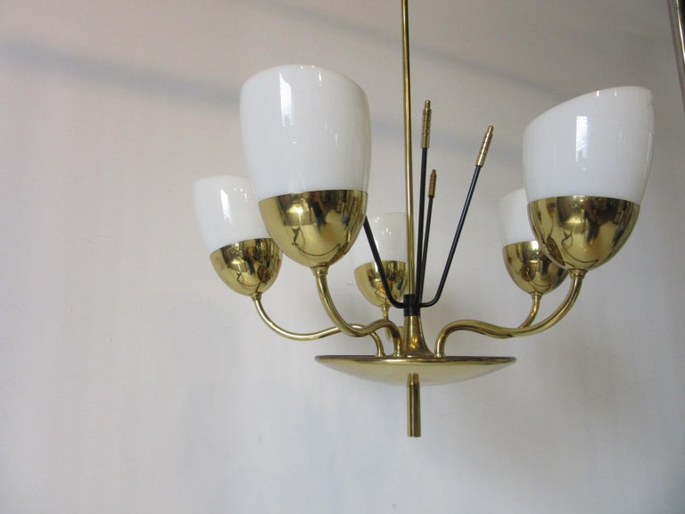 A fine and well crafted brass and milk glass chandelier with six arms, removable shades and detailed stems that come out of the base. Retains the manufactures label made by the Majestic M.S.& S. Company New York. Formally the Majestic Lamp and radio