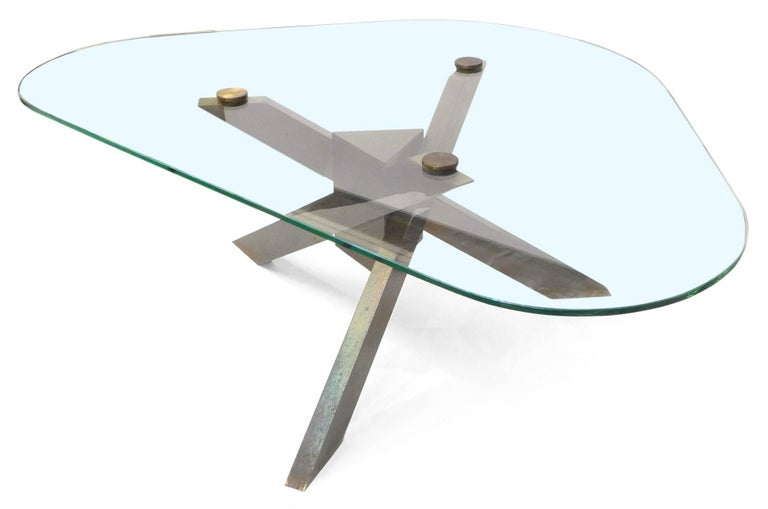 A wonderful, geometric brass and glass coffee table. A beautifully constructed tripod leg structure made of rectangular stock brass tubes, radiating off of a central triangular hub. The original, symmetrical triangular glass top has soft radiused