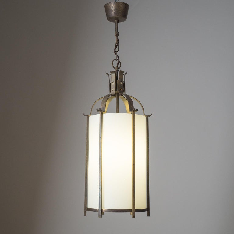 Fine Art Deco brass lantern from the 1930-1940s. Cage-like brass structure with a tubular glass diffuser with white inner casing. Heavy patina on the brass and a few chips on the glass, hidden by the vertical stems. One original brass E27 socket