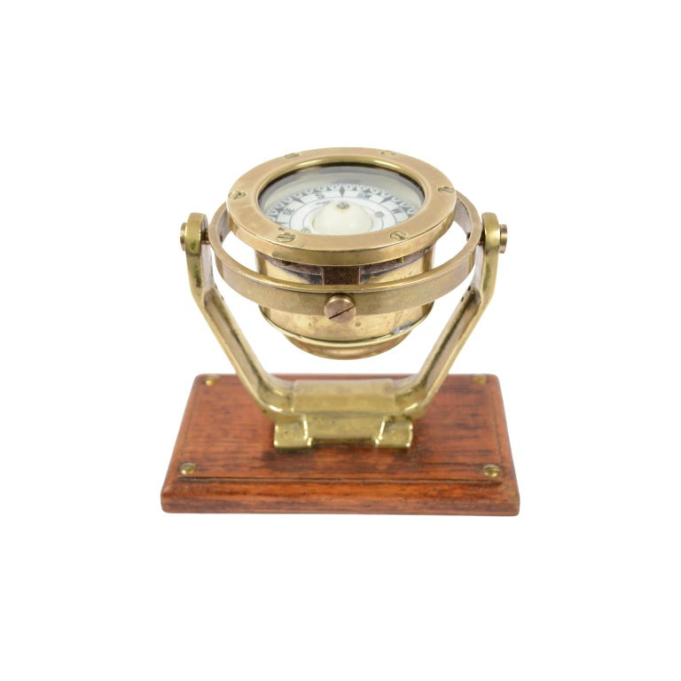 Brass and glass nautical compass on universal joint signed Coubro & Scrutton Ltd London from the second half of the 19th century and mounted on oak wooden board. The compass consists of a brass and glass vessel on the bottom of which is fixed a