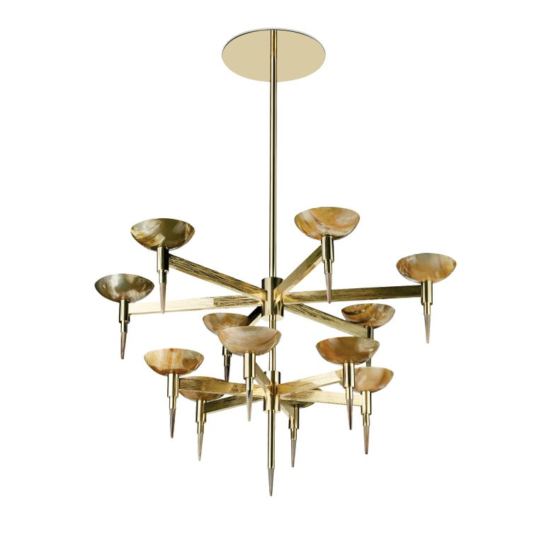 A modern interpretation of the traditional chandelier, the luxurious materials of this bold piece create unique lighting effects. Entirely handcrafted of brass, the two-tiered structure extends from a polished cylindrical pole with 12 arms extend -