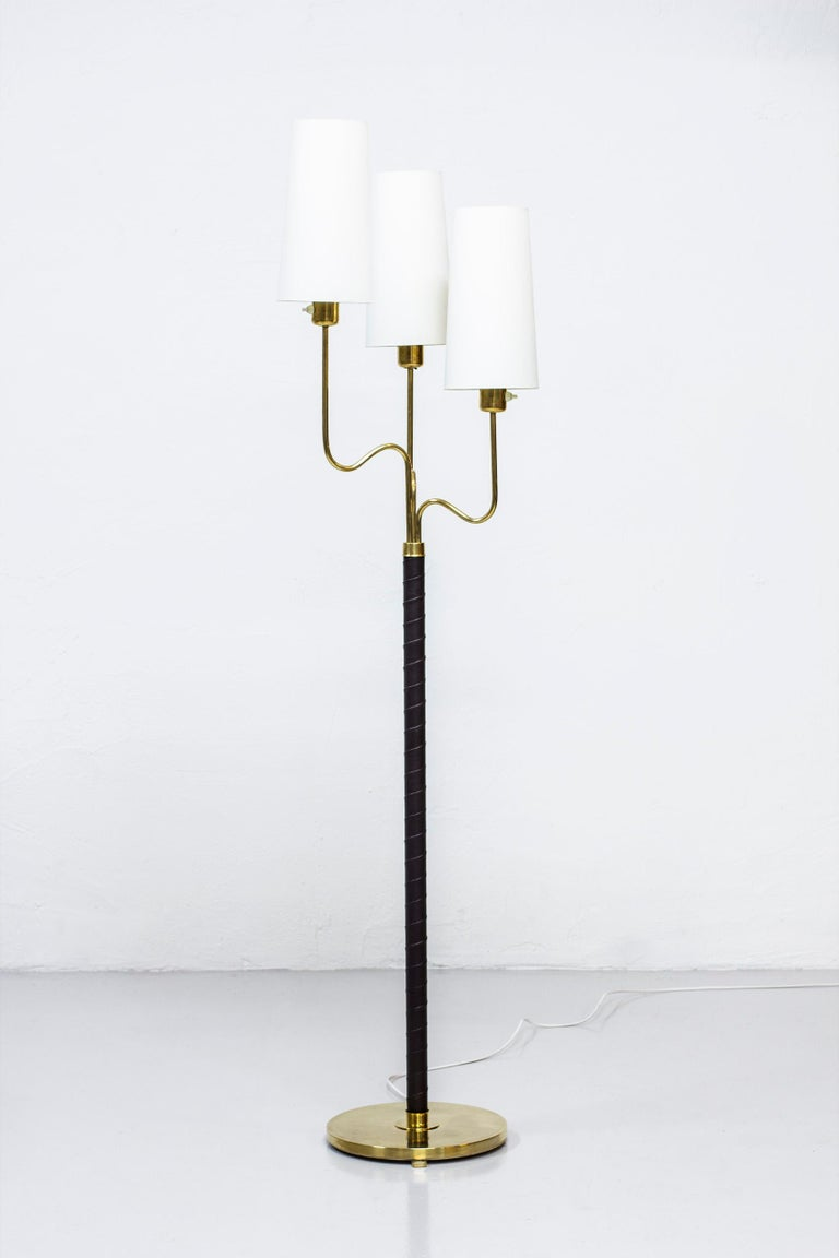 Floor lamp designed by Hans Bergström. Produced by ASEA in Sweden during the 1940s. Polished brass, aubergine/dark brown leather and chintz fabric shades. Light switches on each lamp in working order. Very good vintage condition with some signs of