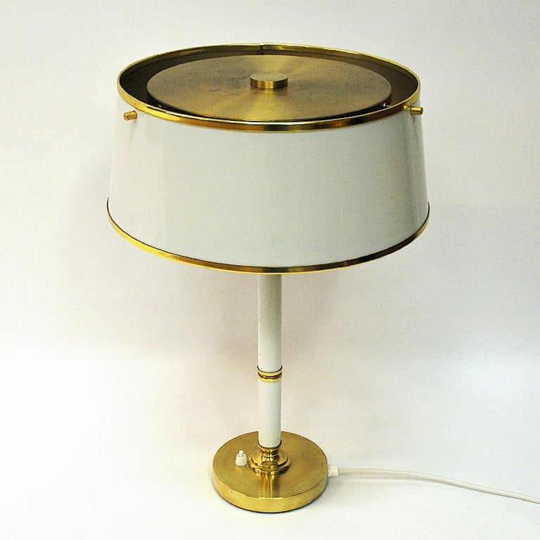 Great Swedish table lamp made by Borèns in Borås, Sweden, 1960s. This midcentury lamp has white lacquered metal shade and trunk - and brass decorations. Brass foot with the light switch. Big round lamps shade and brass top. Two light points gives