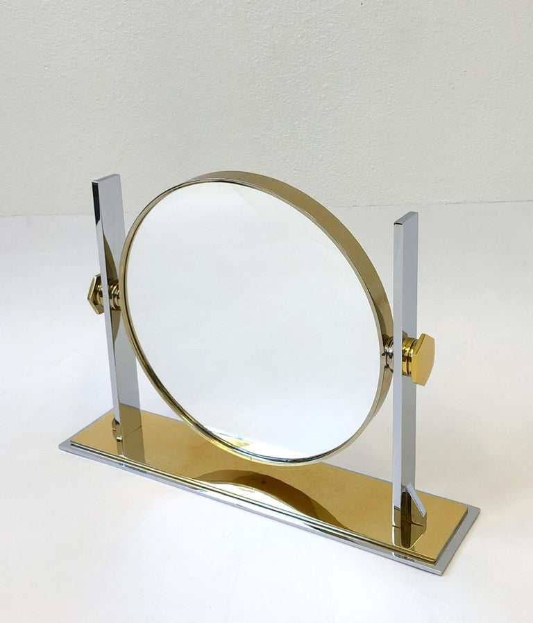 A spectacular polish brass and polish nickel vanity mirror designed by Karl Springer in the 1980s. The mirror can be tilted. The back of the mirror is convex.