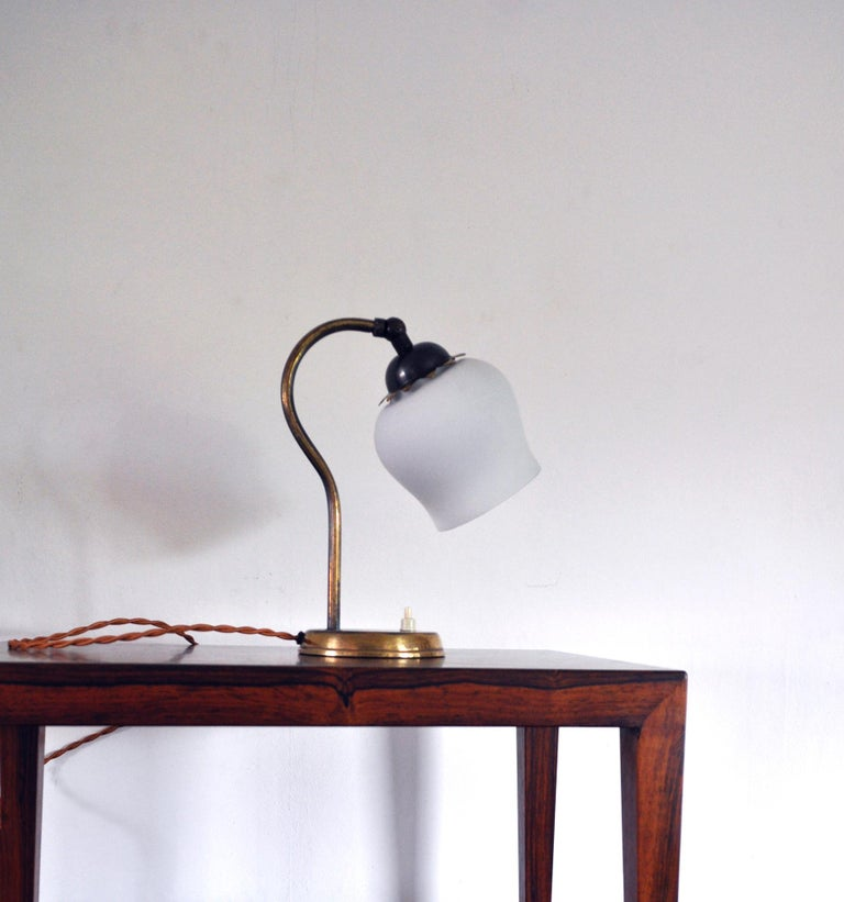 Brass and opaline glass Art Deco table lamp, Scandinavia 1930s. Adjustable lamp shade. Fine vintage condition with patination, signs of wear consistent with age and use. Small chips on the glass shade. Light source: E27 Edison screw fitting,