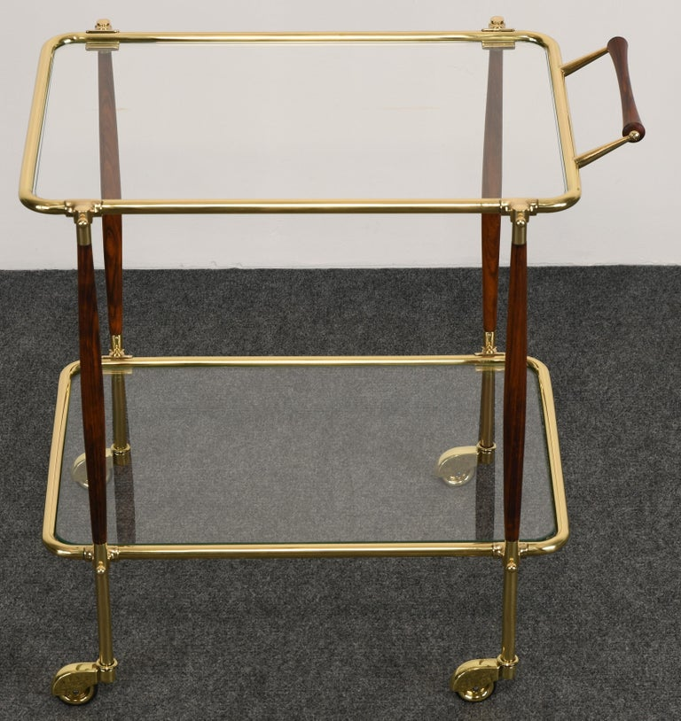 A gorgeous brass and rosewood bar cart or tea cart in the manner of Cesare Lacca. Newly restored finish. Glass is original but has some scratches, however, not distracting.   Dimensions: 27.38