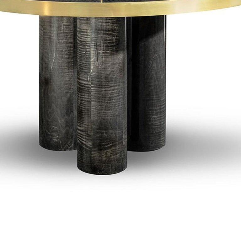 Ray dining table  The RAY dining table is presented with a sturdy figure. The delicate brushed brass lines define and give dimension to this finest design handmade with high gloss grey figured sikomoro. A bold and statement dining table that