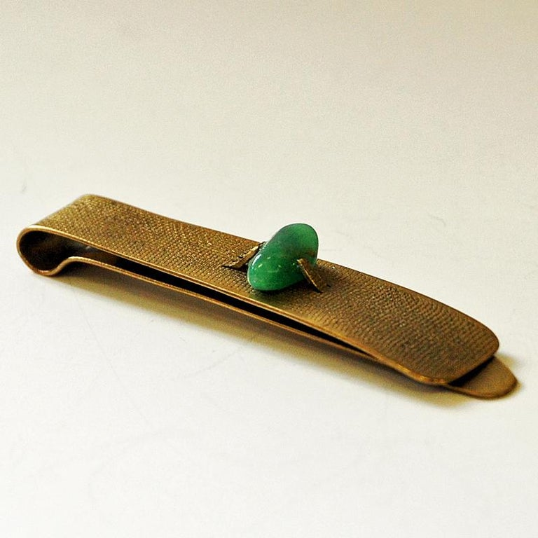 Vintage brass tie pin with a sea green stone on top. Designed in the style of Anna Greta Eker, Norway, 1960s. Rought surface. Scandinavian midcentury design. Measures: 7.5 cm L x 1.5 cm W. Good vintage condition.