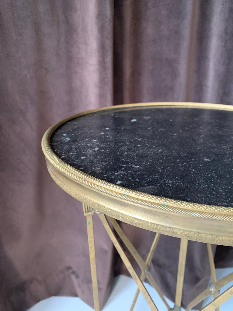 A handsome claw footed brass and black stone neoclassical Guéridon style table.