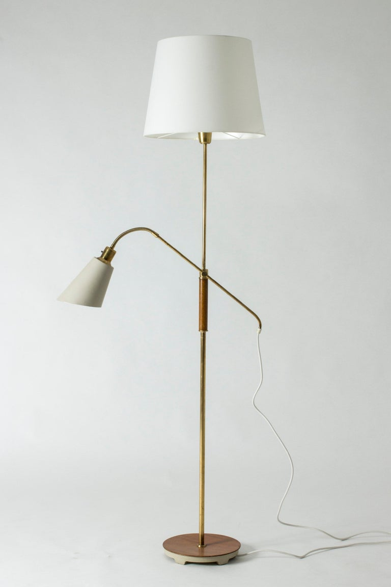 Cool floor lamp by Bertil Brisborg, made from brass, with lacquered metal and wood details. One lamp shade spreads a nice, general light, while the lacquered shade gives direct light, for example for reading. The lacquered shade can be moved