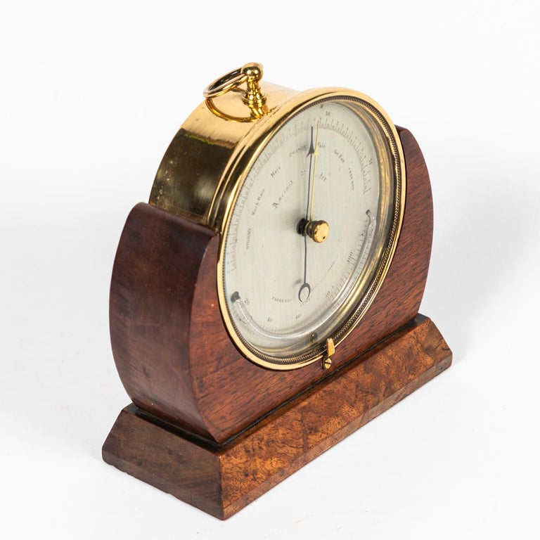 Brass barometer resting in a wood base from mid-19th century England engraved,