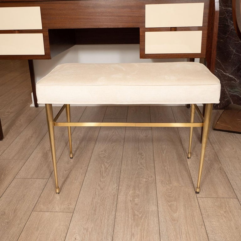 Brass bench with tapered and fluted legs.