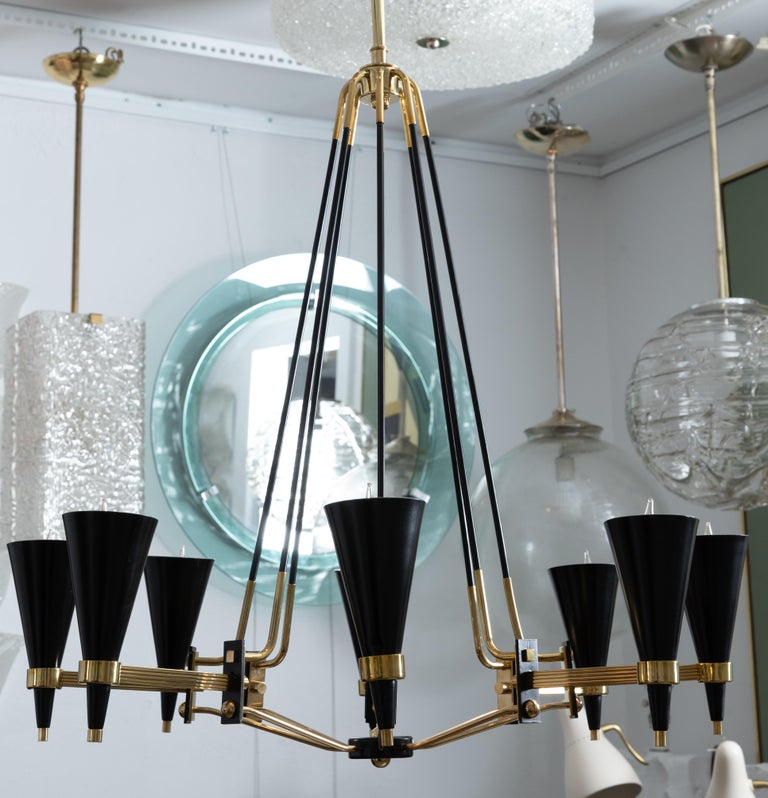 Brass and black enameled metal eight arm chandelier featuring conical shades By Stilnovo.