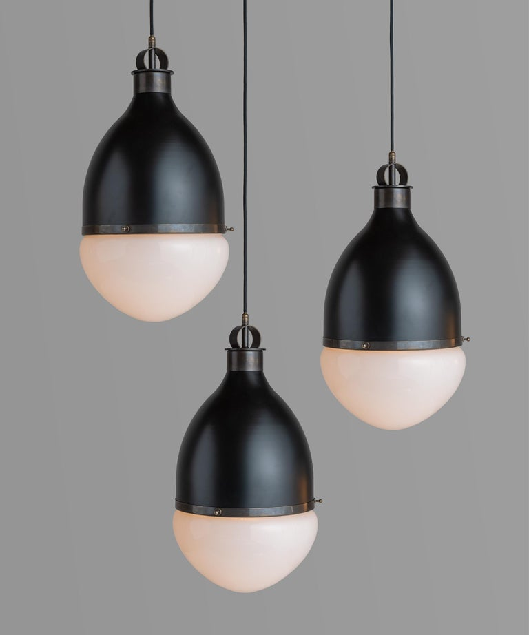 Brass andblack metal pendant, Italy, 21st century.  Large scale hanging pendant with brass details and frosted glass shade.