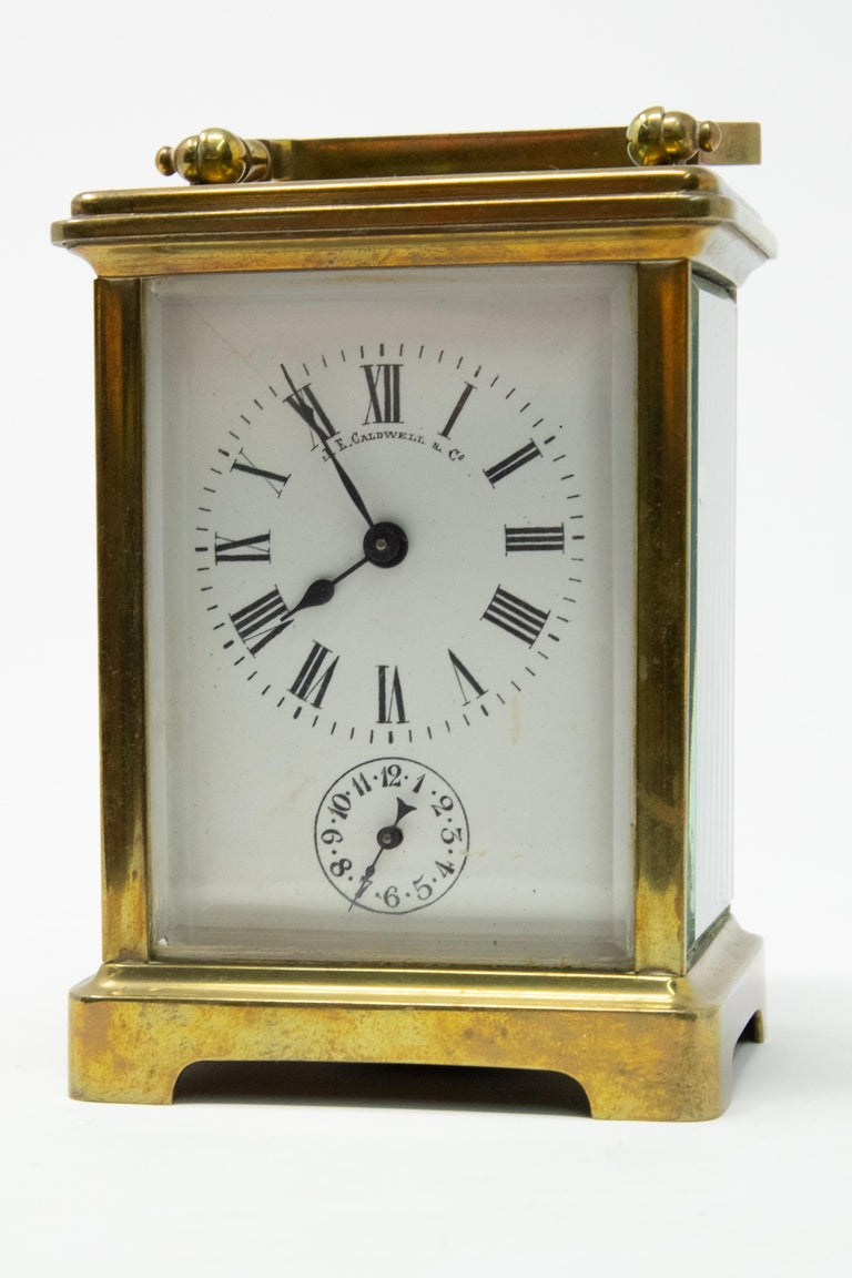 Offering this magnificent carriage clock by JE Caldwell & Co. stands on a bracketed foot with beveled glass all around. The clock face is simple black and white. The key is with the clock, it does wind up and work. Keeps time pretty accurately. Also