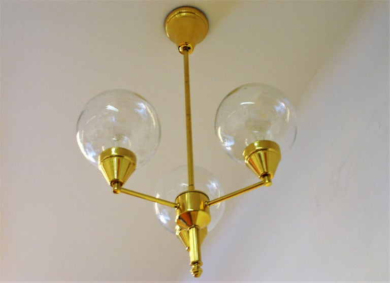 Brass ceiling lamp with three clear glass domes in upward position. Probably a Swedish lamp from circa 1960s. The glass domes have small closed air bubbles. Brass base. Lovely vintage lamp. Signed AJH.