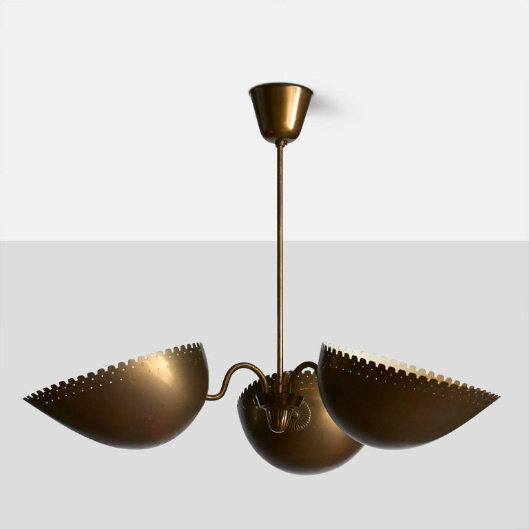 A wonderful aged brass pendant from Sweden by Bertil Brisborg for Bohlmarks. The lamp has three shades with serrated and perforated edges, facing upwards. The lamp is marked by Bohlmarks, Sweden, circa 1940s.