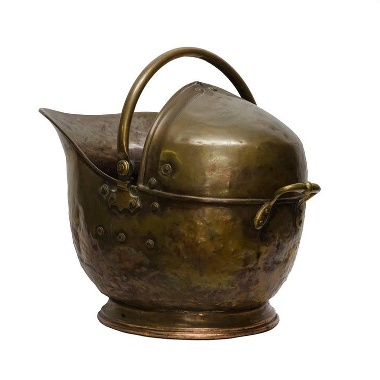 This 1880s era coal bucket is a beautiful antique accent for any fireplace. The decorative mountings, with both a rear and top handle, and traditional helmet style make for a graceful form with great functionality.