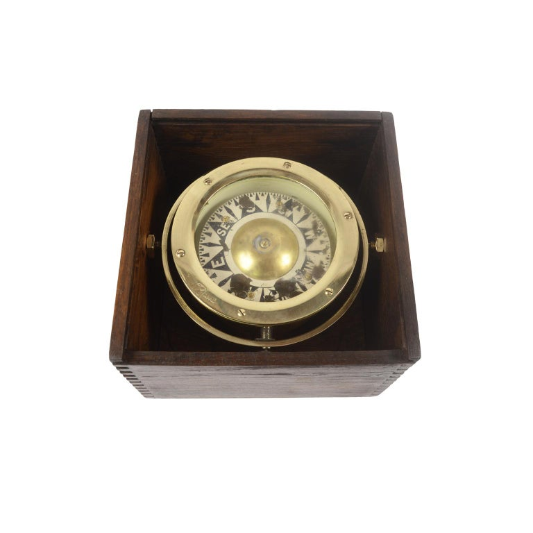 Magnetic compass on universal joint in its original wooden box with slot lid, signed with a trade mark brass emblem engraved with two crossed arrows within a shield, from the end of the 19th century. The compass consists of a cylindrical vessel in