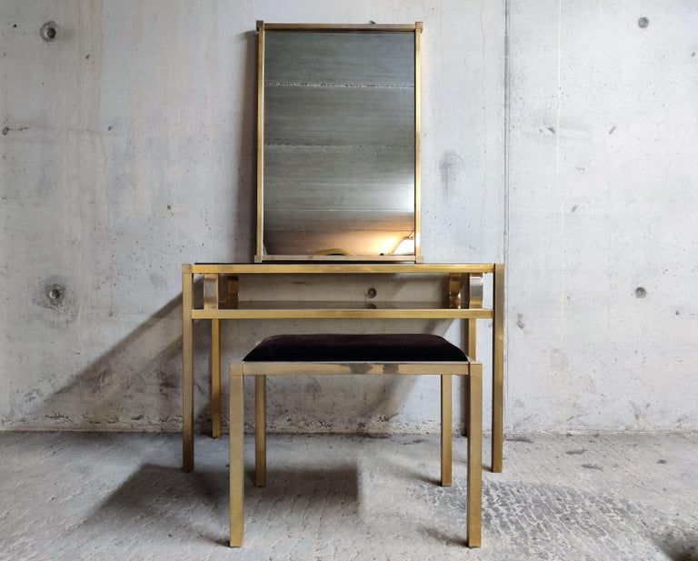 Vintage brass console table with matching mirror and stool.  The console table has crystal smoked glass tops.  The console table is in original untouched condition as is the mirror and the stool.  Beautiful set, ideal for a hallway or