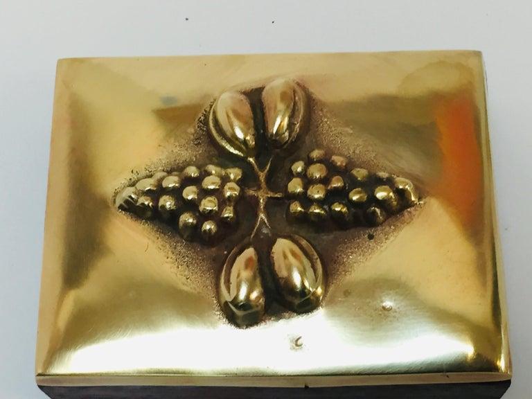 Brass decorative trinket box. Handcrafted trinket box with lid wood bottom and brass decorative lid. Handcrafted trinket box with lid. The top of the lid decorated with embossed grapes. Handcrafted in Europe, Switzerland.
