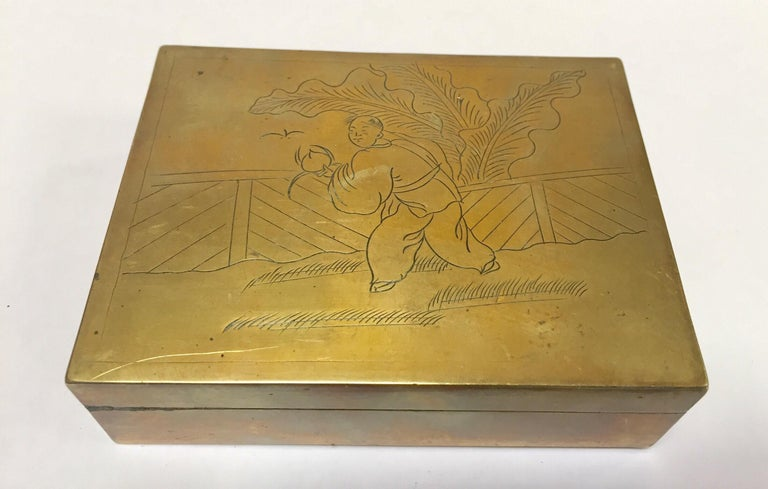 Brass decorative trinket box. Handcrafted trinket box with hinged lid wood bottom lined. The top of the lid decorated with hand chased Chinese man wearing traditional clothes scene. Handmade in China. DIMENSIONS H 1.25 in. x W 4 in. x D 3 in.