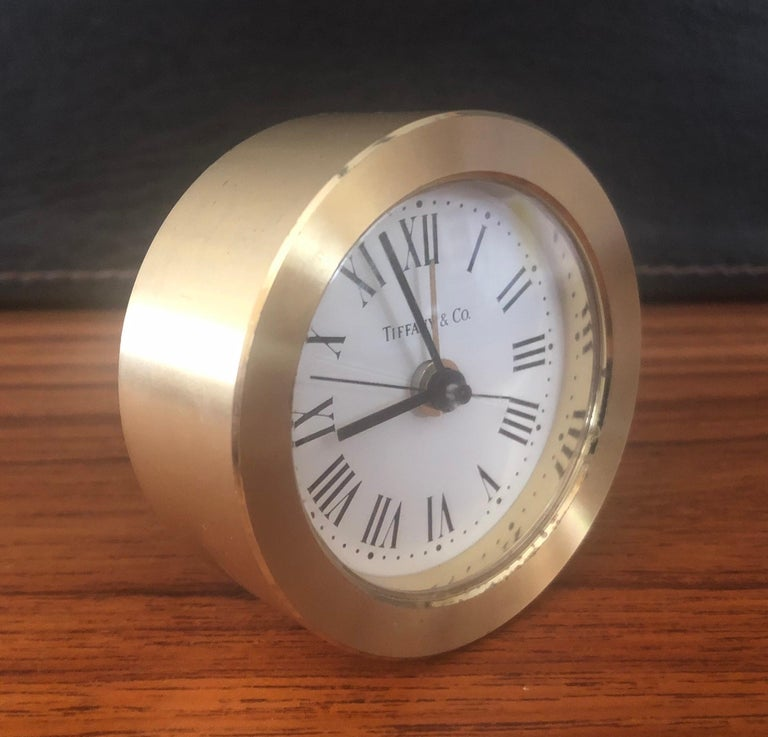 A very nice round brass desk alarm clock by Tiffany & Co., circa 1980s. The clock has a quartz movement and is made in Germany; the case is made of brushed brass and has formed Roman numeral for hour markers. The piece features a white dial with