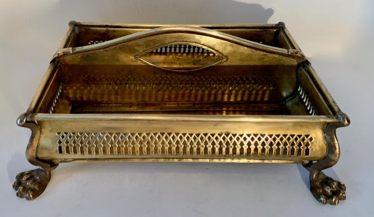 A handsome vintage brass, two-compartment caddy well suited for the vanity, food display, mail or even plants... a wonderfully designed piece sporting lions feet and intricately cut sides for great eye appeal. A wonderful desk accessory or catering