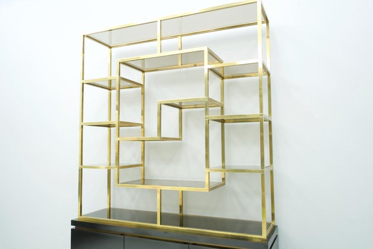 Great shelf or room divider by Kim Moltzer, France, 1970s. Brass shelf with many smoked glass floors, sideboard, black laced with 3 doors.  Very good condition.