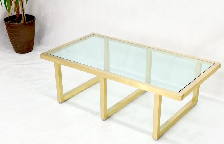 Heavy gage bolted together machined brass frame glass top coffee table.