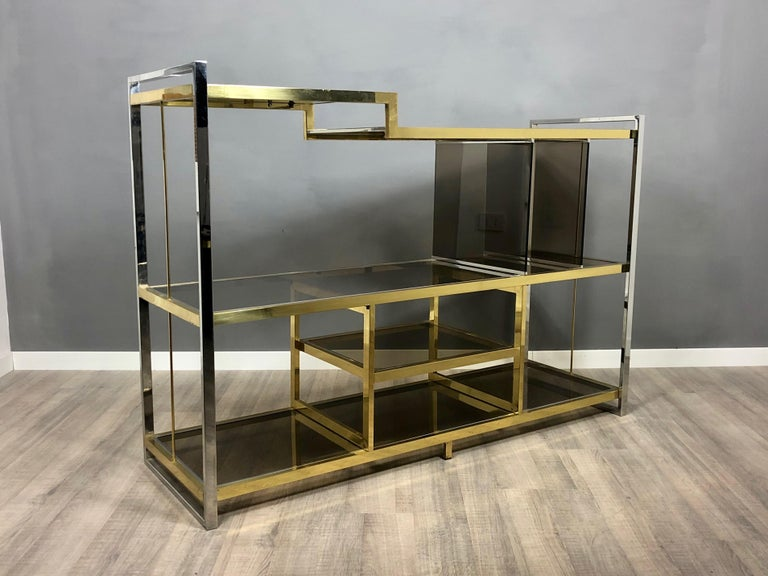 Console/sideboard in brass, chrome and smoked glass. Designed by the Italian Serantoni & Arcangeli for New Ideas Inox, circa 1970s, Italy.  It has its original target.  Condition are excellent, light wear due to age and use, as the photos