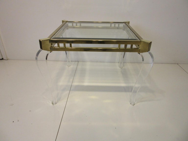 A side table with brass top frame having sculptural Lucite legs and a inserted beveled glass drop in top in the manner of Charles Hollis Jones. A very stylish modern look with a light feel that can work in many different types of interior settings.