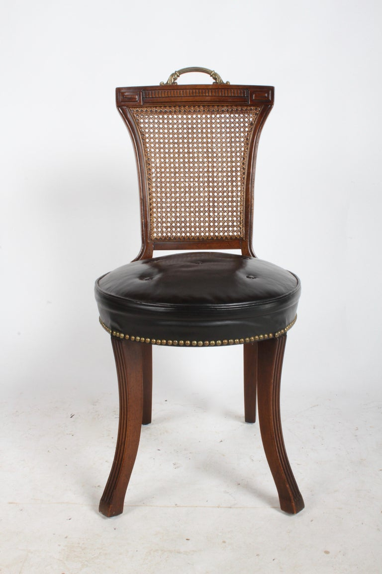 In the style of Grosfeld House mahogany frame desk chair with brass handle, caned back, Greek key design, splayed fluted legs and black leather seat. Original leather seat, has some stress marks, four buttons and brass tacks. Original finish, some