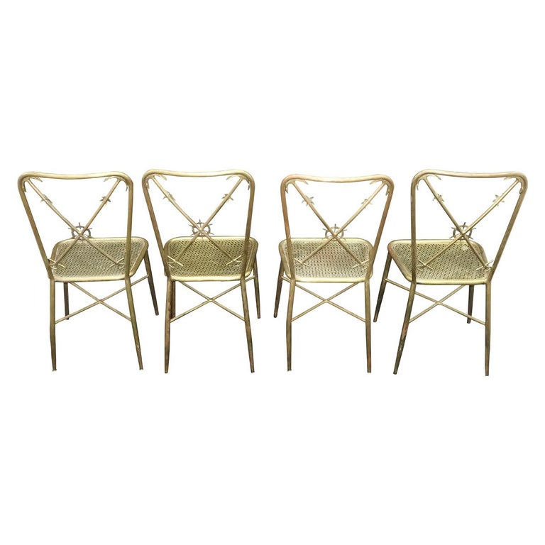 Elegant brass Italian nautical theme side or dining chairs in the manner of Gio Ponti. The backrest has 2 anchor crossbars with a ship wheel motif in the center. The metal seat is reminiscent of the texture used by Mathieu Mategot in his designs.