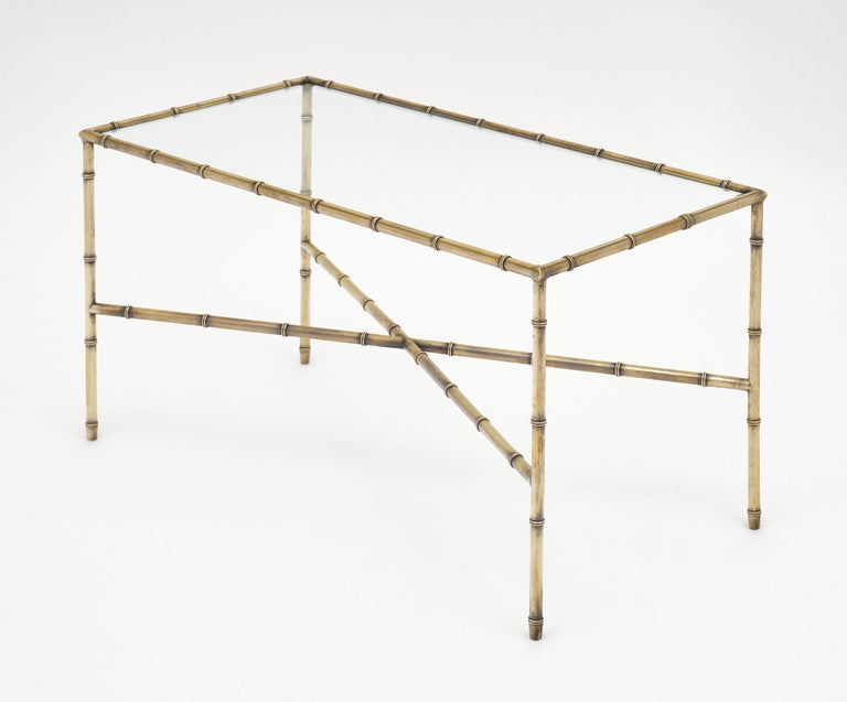 Coffee table from French company Maison Baguès with a gilt brass frame featuring stylized bamboo and a glass top. The x-stretcher adds dimension to this classic yet simple piece.