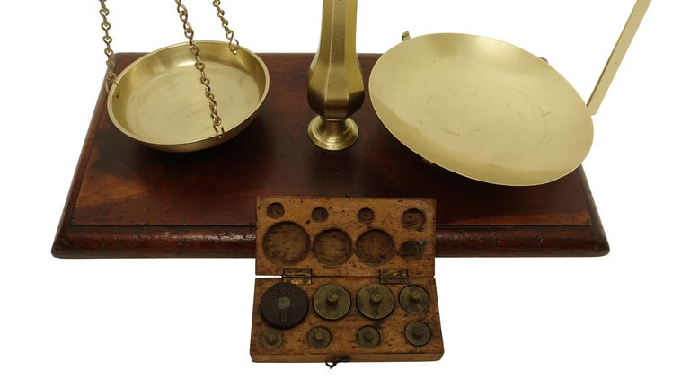 Brass merchants scale on a mahogany base with a full set of boxed weights, England, circa 1870.