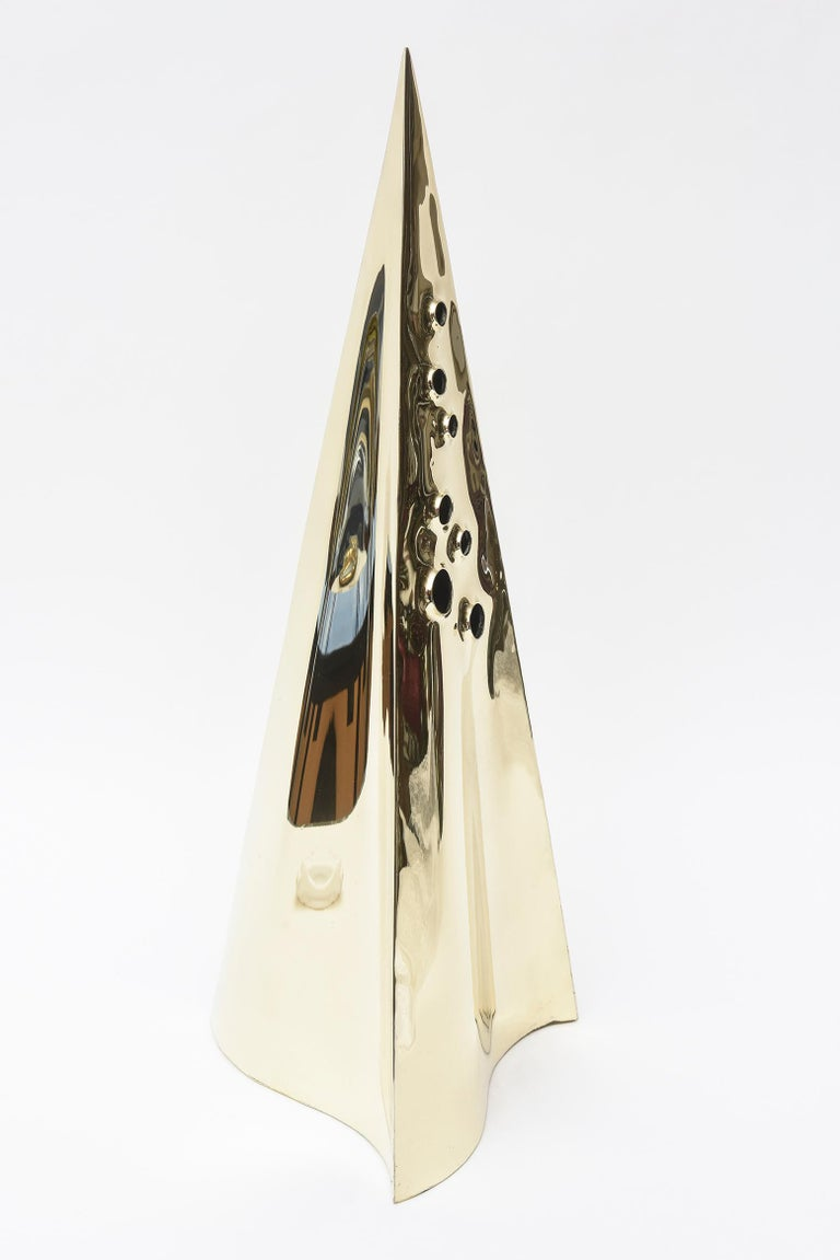 This truly arresting vintage modernist brass pyramid sculpture has been professionally polished. It is in a combination of a tall pyramid and triangle form and has 7 random purposeful holes in the front of different sizes. It was so well made at the