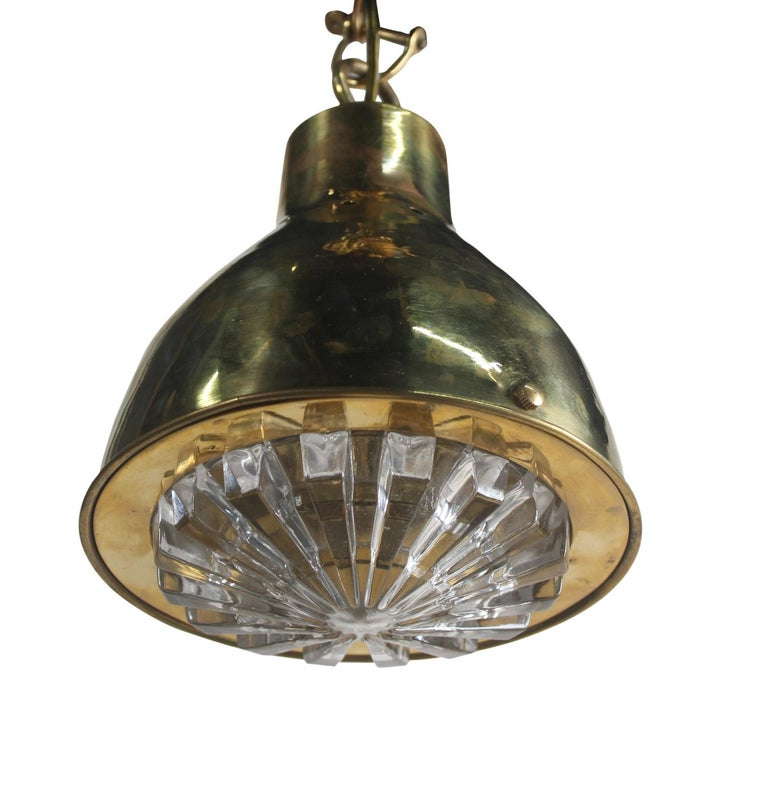 A brass ship's pendant light with a textured glass Fresnel lens shade, 1970s. Takes a standard base light bulb and comes with 4' of brass chain and ceiling canopy. Rewired for American use.