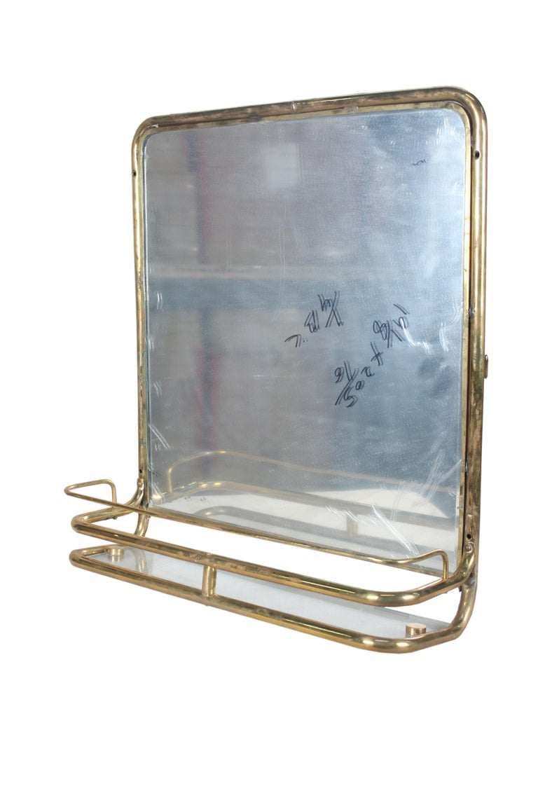 A brass wall mirror from a decommissioned ship's stateroom. Features a clear glass shelf and double brass