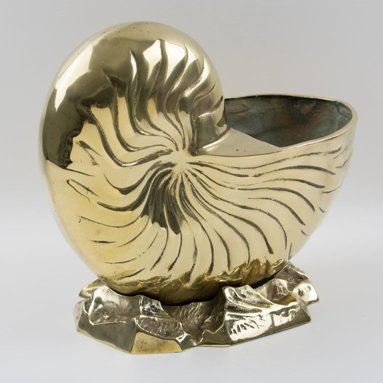 Stylish modernist polished brass wine cooler or vase or even planter, cachepot, a complete versatile use. This ultra-chic decorative piece features a whimsical sculpture of a large nautilus shell standing on a stylized sea base. Lots of character,